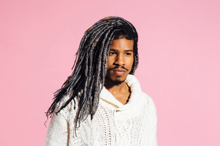 A man with dreadlocks is wearing a cozy sweater