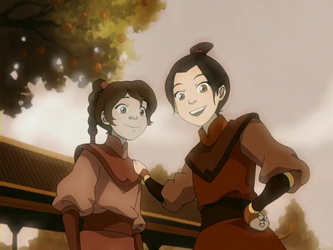 A girl with a long ponytail and a puffy shirt stands next to another person with a bun in their hair