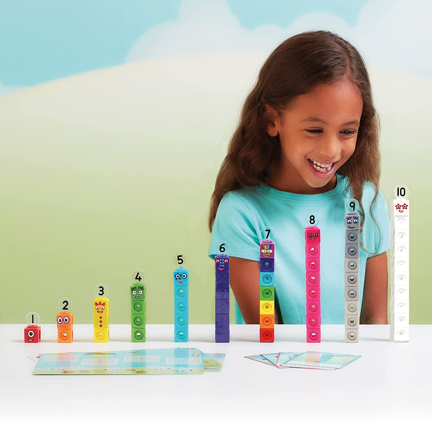 Child model playing with stacks of Numberblock toys