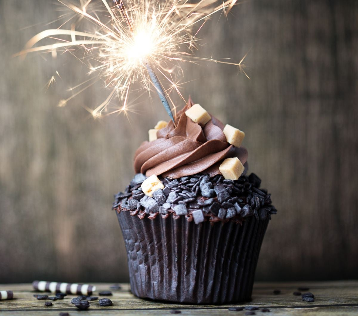 A chocolate cupcake with chocolate curls and a sparkler on top