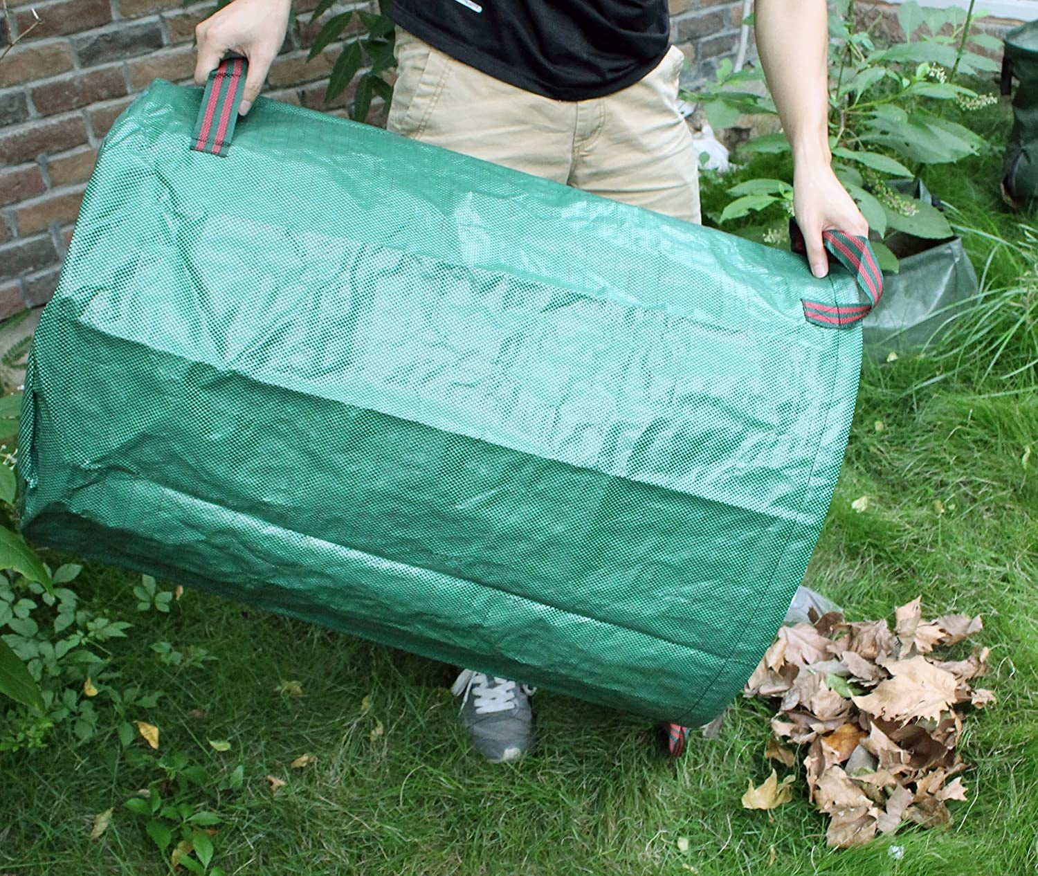 hands holding the green cylindrical bag as a scoop for dead leaves