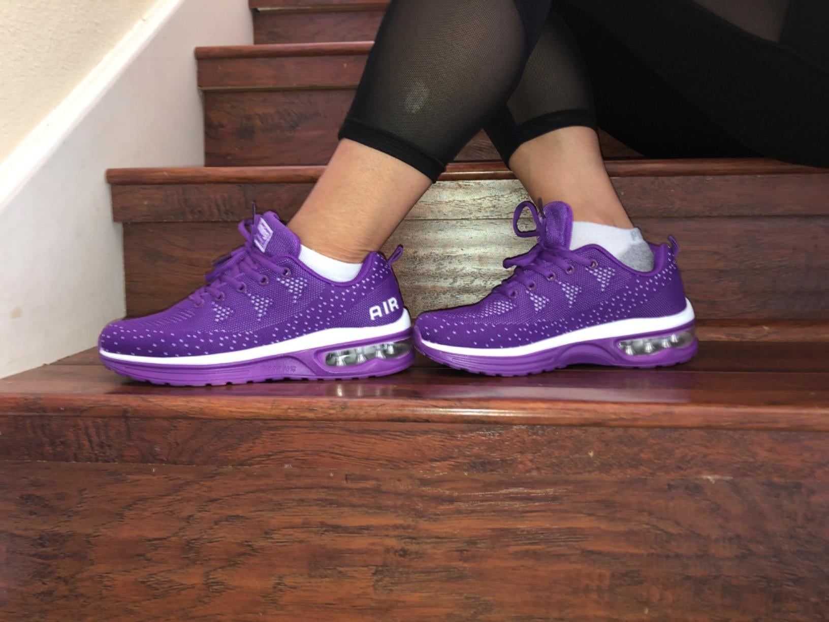 Reviewer show side view of purple STQ running shoes