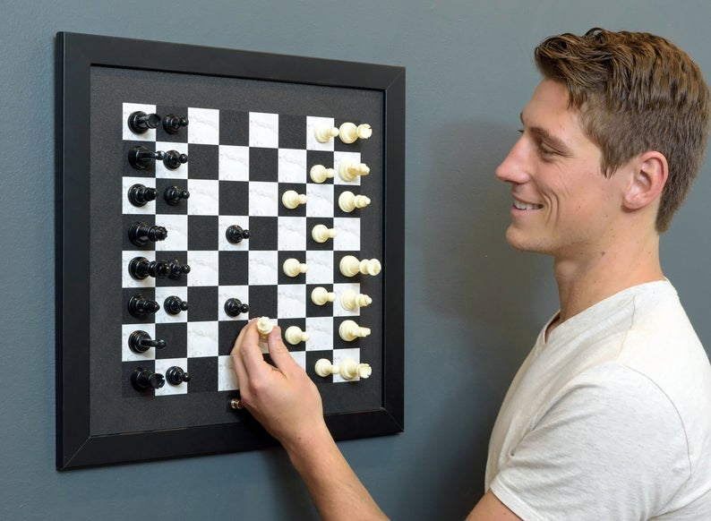 model using the framed chess board on a wall