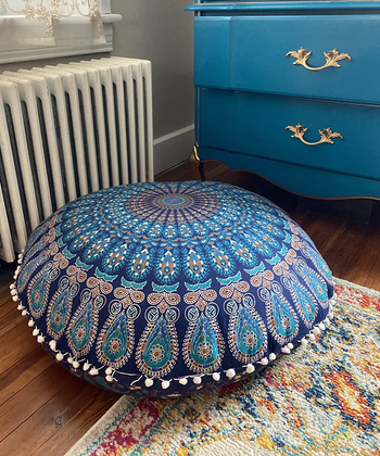 a reviewer photo of the pom-pom trimmed floor pillow cover on a pillow that's sitting on the floor