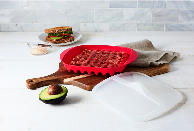 the red tray with grooves and bacon in it and plastic lid next to it