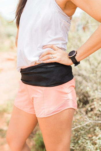 Model wearing black fabric belt over their shorts