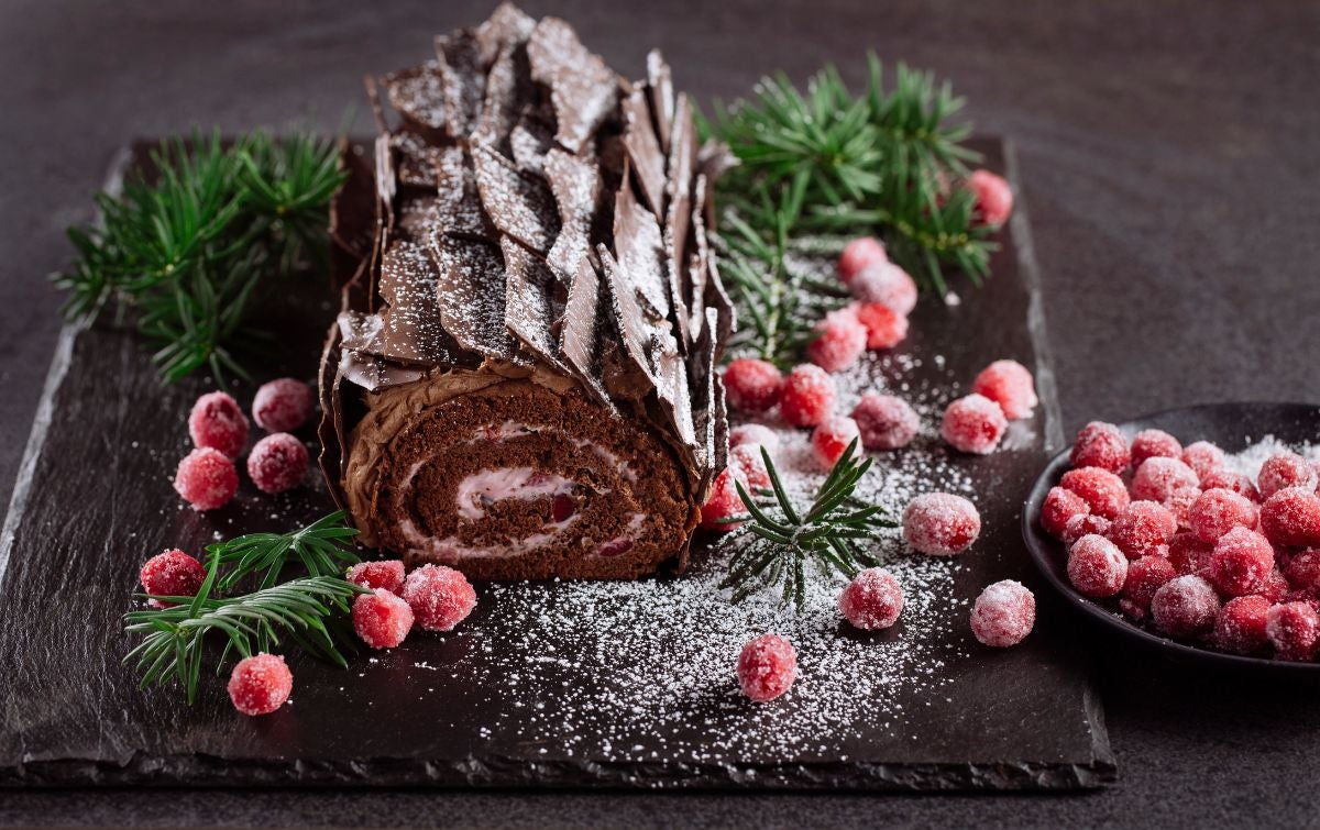 A yule log cake with candied cranberries