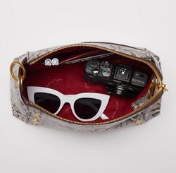 inside of the handbag with sunglasses, a camera, and pens inside