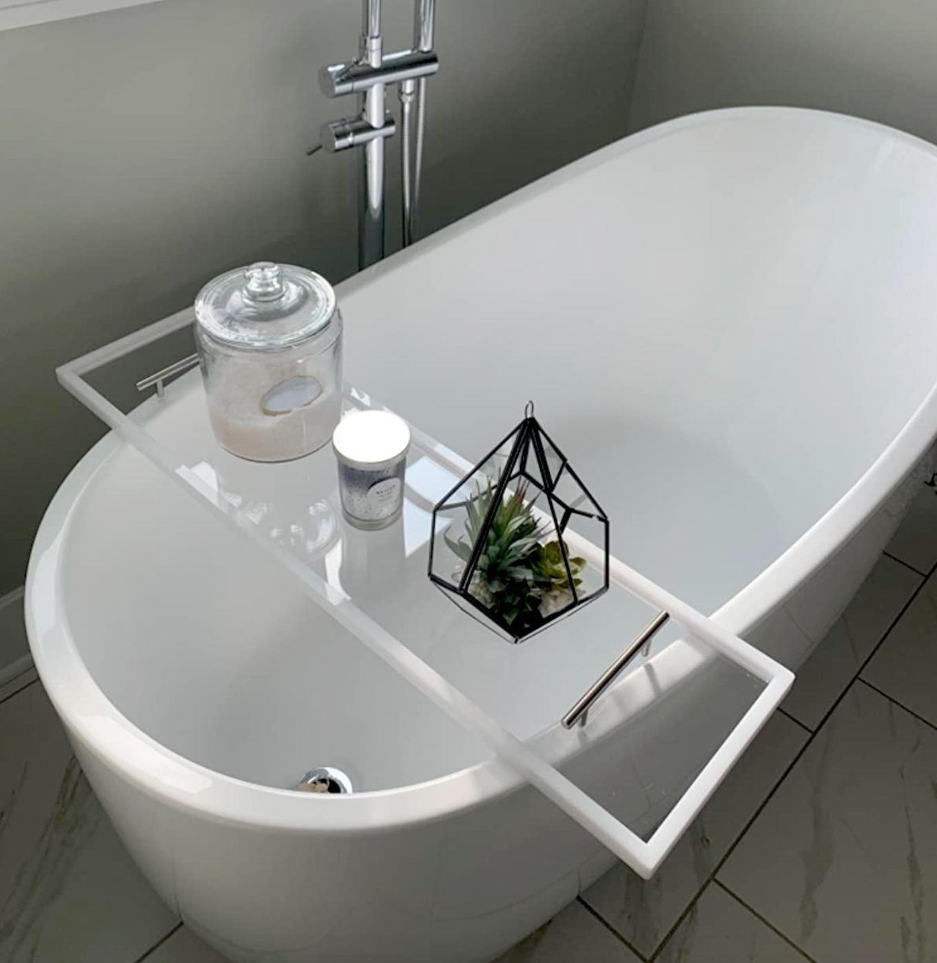 clear tray added over bathtub and styled with a plant, candle, and bath salts