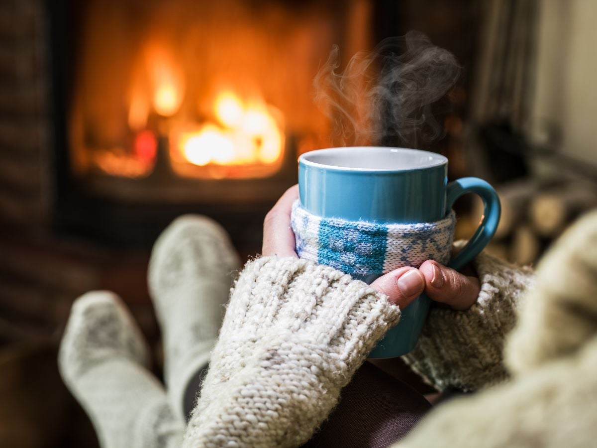 Someone holds a steaming mug and puts their feet next to a fireplace