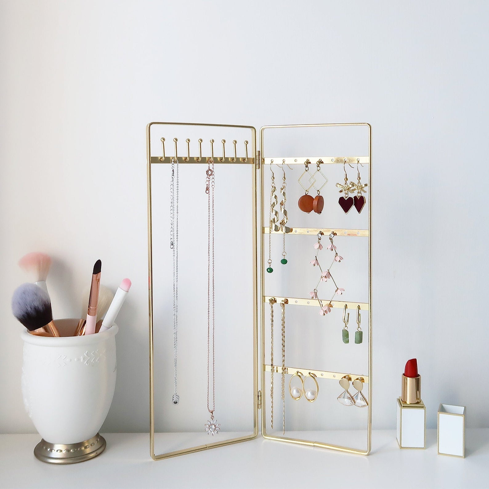 The gold bi-folding jewelry stand on a counter with baubles hanging off it