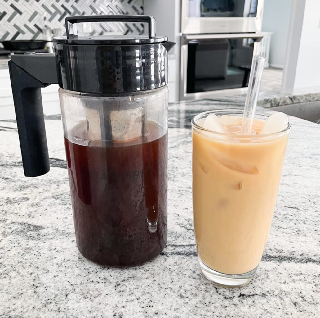 Cold brew coffee pitcher next to an iced coffee drink