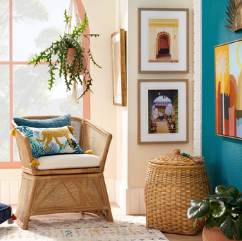 a living room with the pillow sitting on a wicker armchair