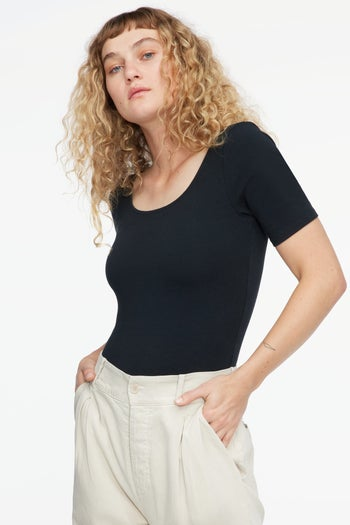 front view of a model in the black scoop-neck bodysuit