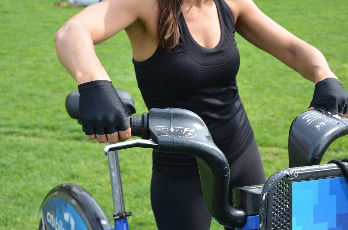 model wears gloves in black to ride a bicycle
