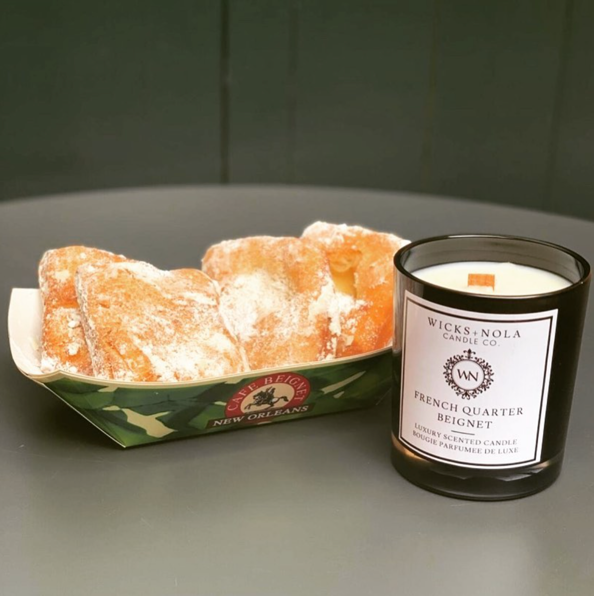 The French Quarter Beignet candle is displayed next to a serving of beignets