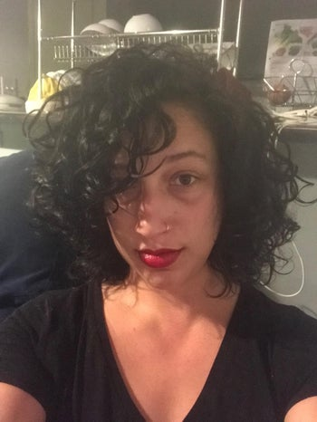 reviewer selfie with black curly hair, red lipstick