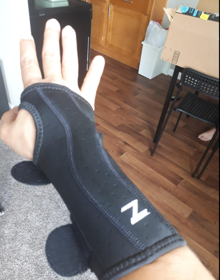 Reviewer in black brace that extends from mid forearm to the upper hand with cutouts for fingers