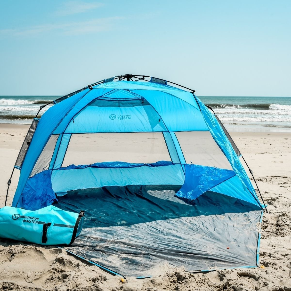 blue pop-up tent on the beach