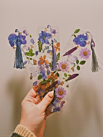 hand holding three clear bookmarks with laminated pressed flowers