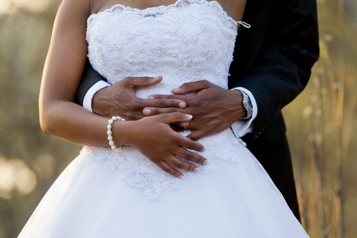 A man stands behind a woman and is holding her hands. They are wearing both a wedding dress and suit