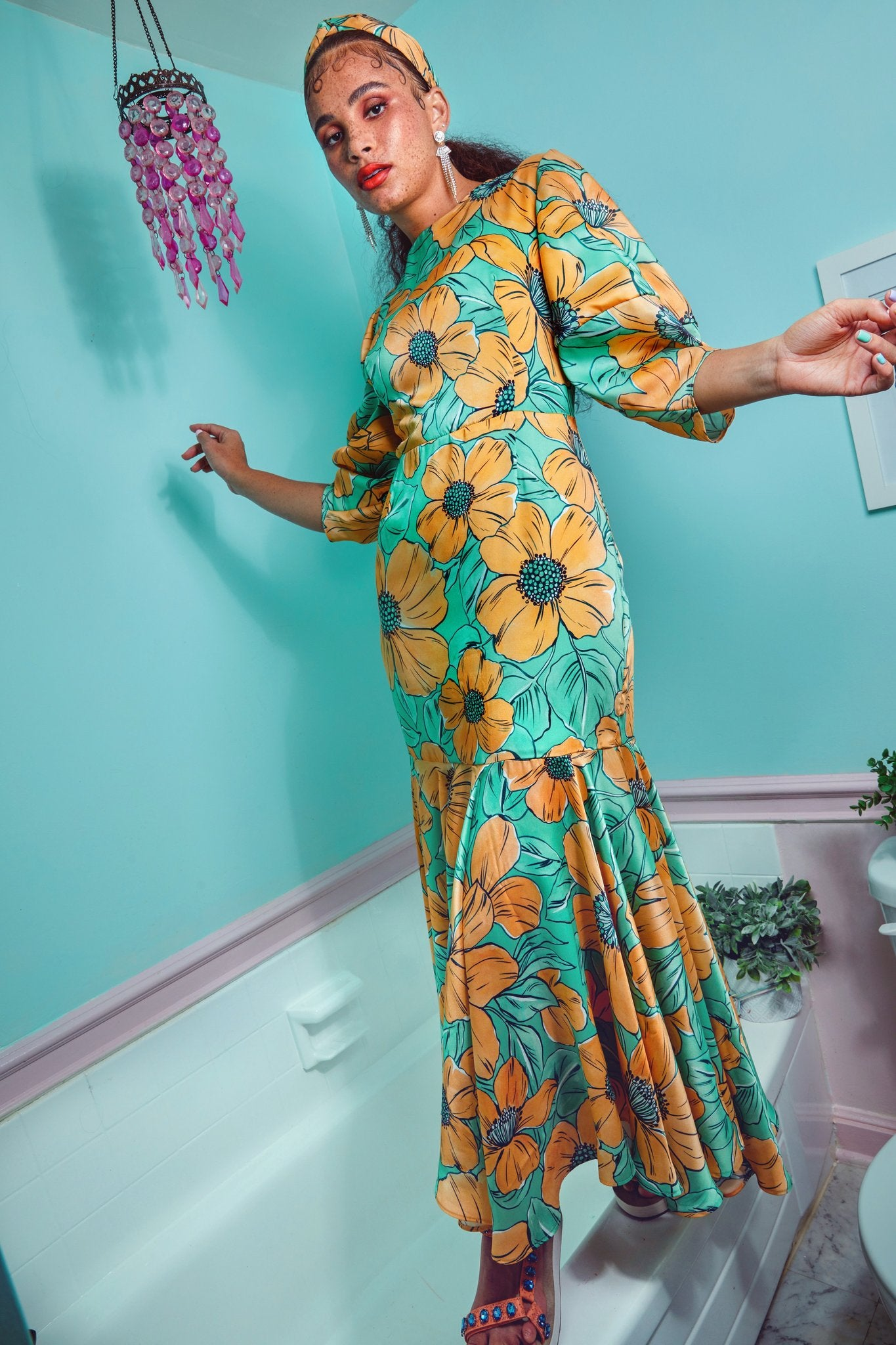 model in teal and orange dress with bold flowers and voluminous three quarter sleeves