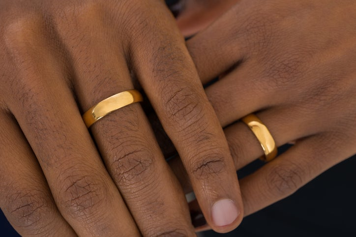 Two men have their hands on top of one another. They both have wedding rings