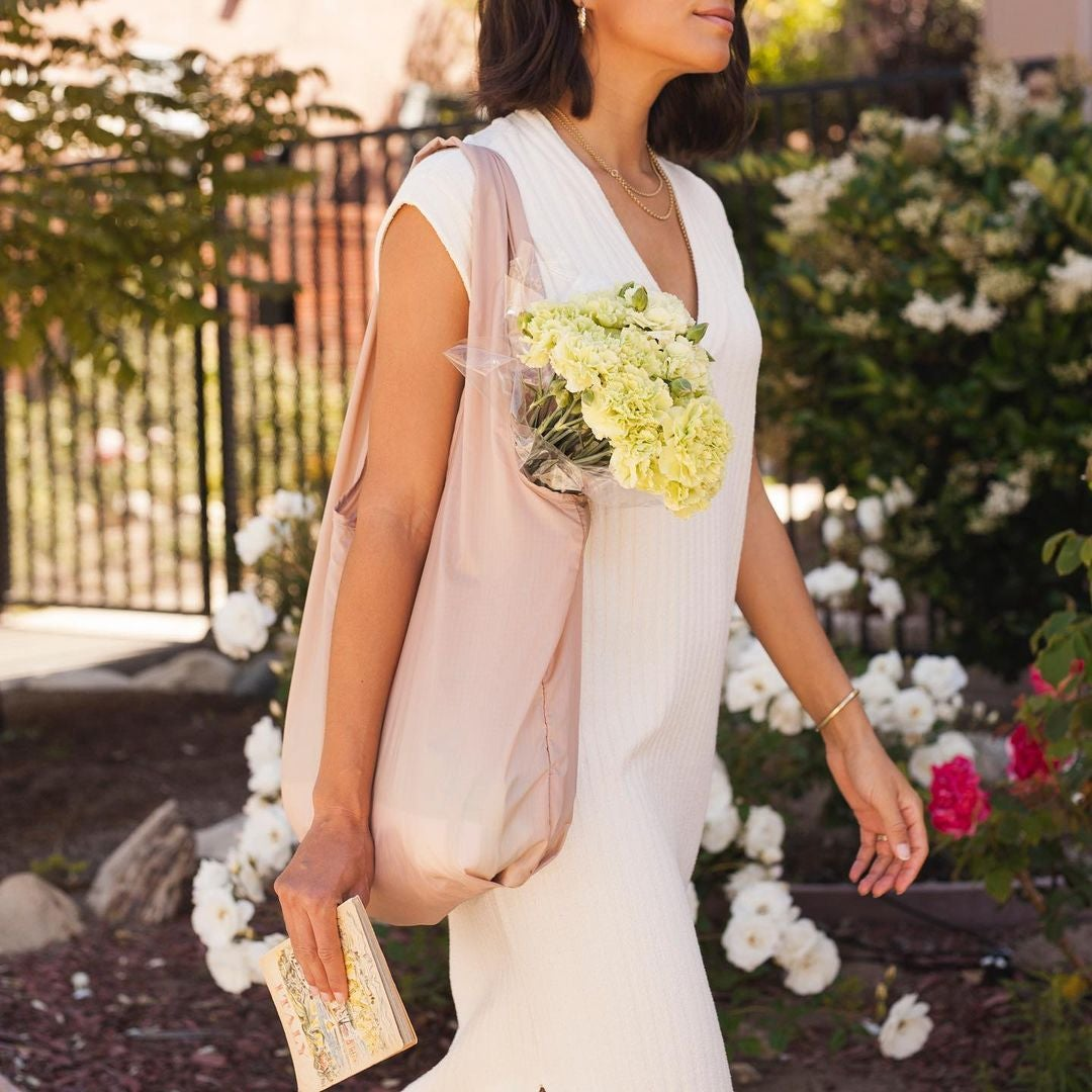 model walking with the light pink tote bag over their shoulder