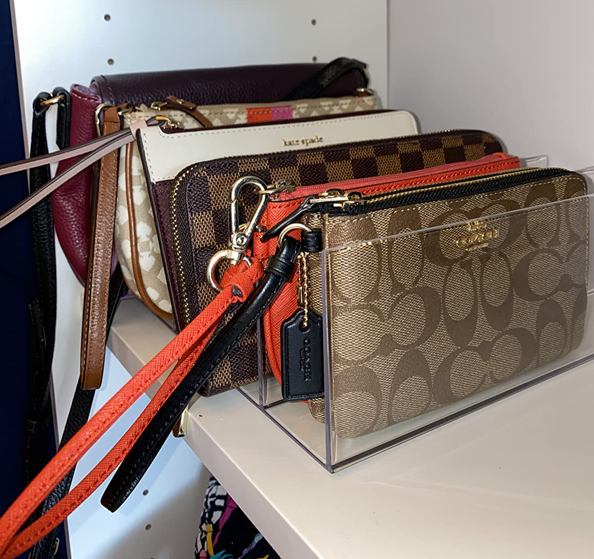 side view of a reviewer's rack holding coach wallets