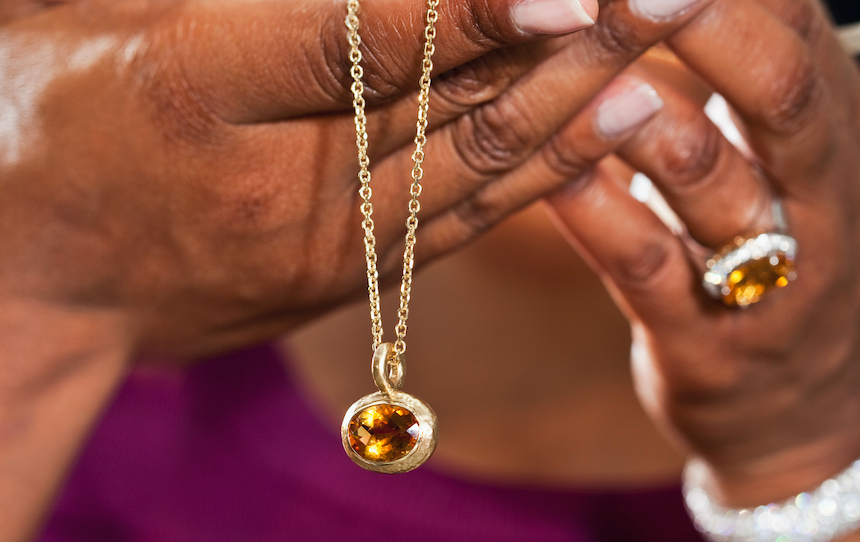 A woman is holding a necklace in her hands.