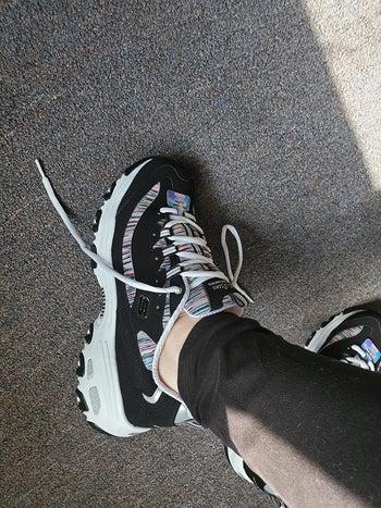 Reviewer wearing Skechers DLite sneakers