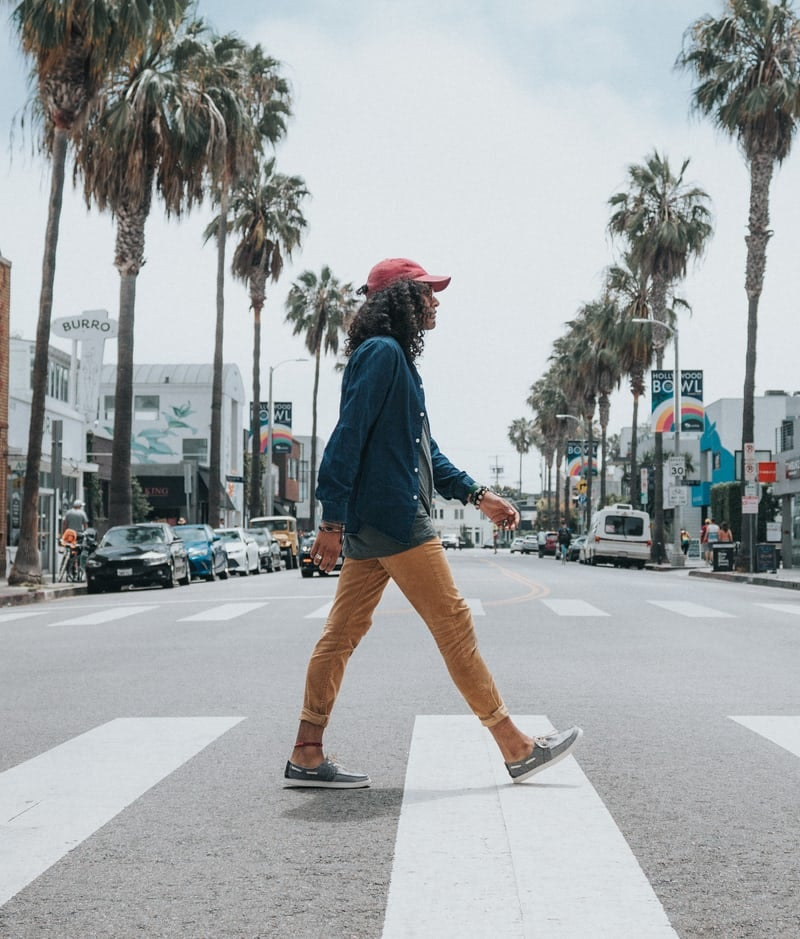 Someone crossing a road with palm trees in the background