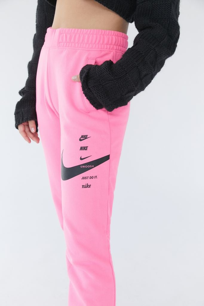 Hot pink nike sweatpants with the nike logo down the side