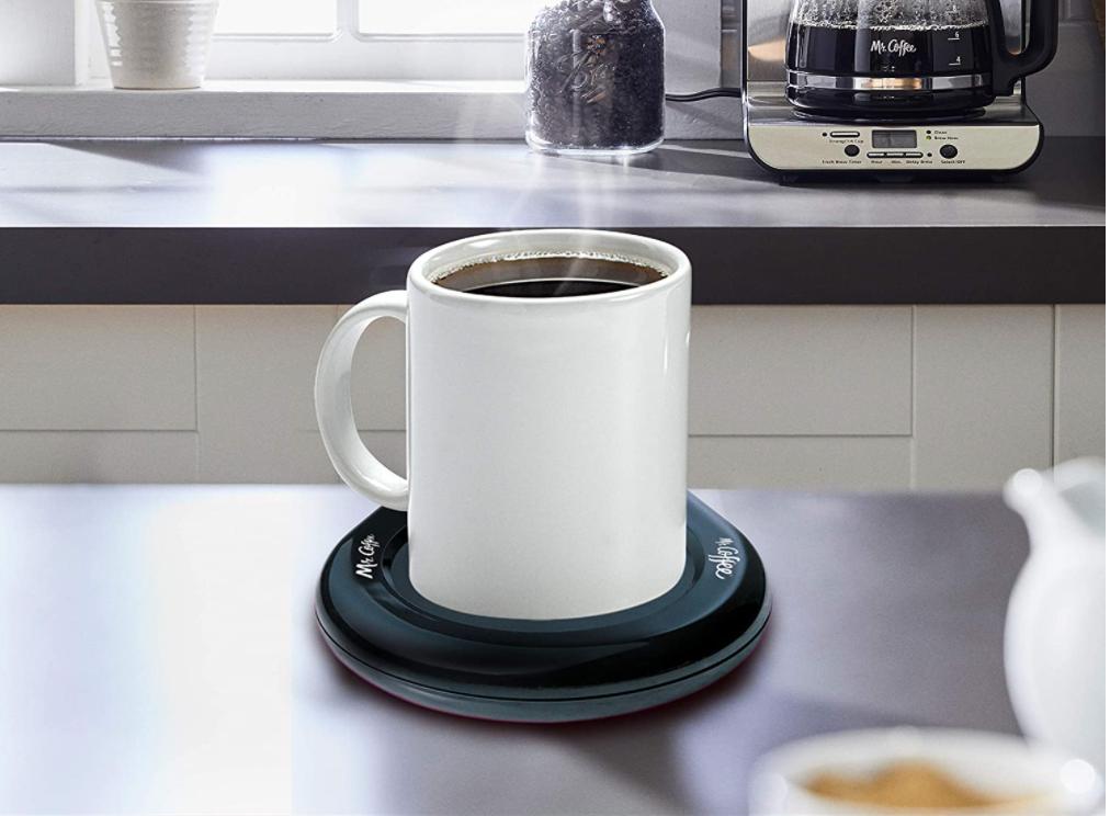 mug of coffee on the black warmer pad