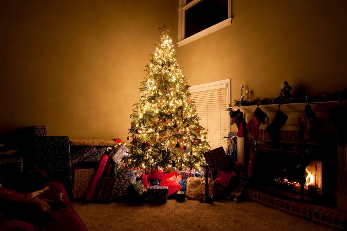 A simple Christmas tree in the corner of a living room, surrounded by presents