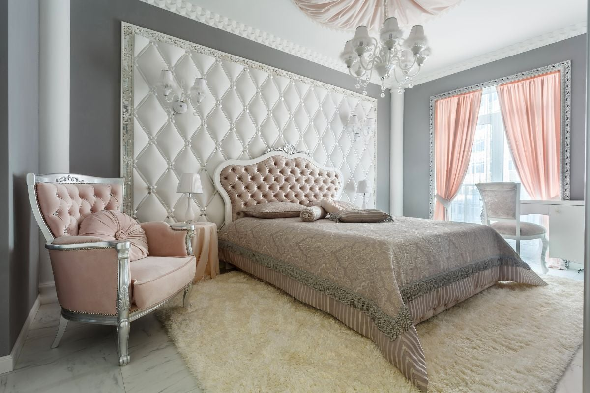 A royal-looking bedroom with marble floors and fuzzy carpet underneath a large bed with a plush headboard, with a window that overlooks a balcony to the side and a chandelier overhead