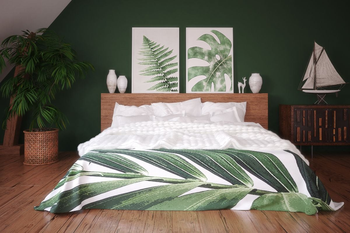 A jungle-themed room with a bed with a plant pattern comforter and two similar patterns as prints on the wall above it with a plant in the left corner and a sailboat figurine in the right