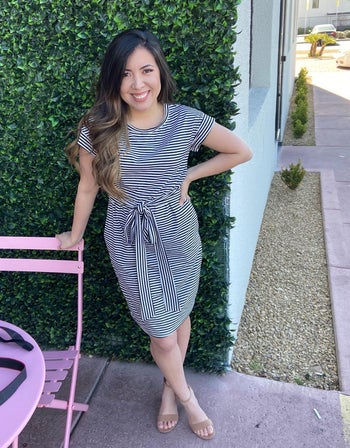 reviewer wearing the navy dress with white stripes with heeled sandals