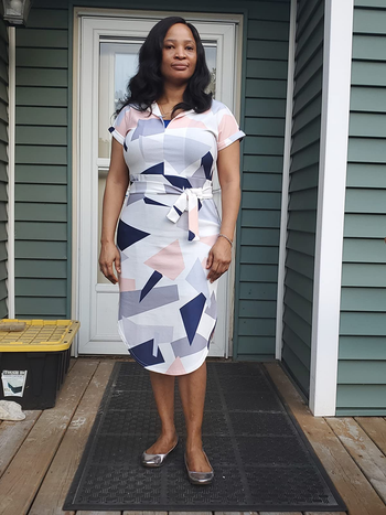 reviewer in the short sleeve tie waist dress in white with gray, peach, and navy shapes