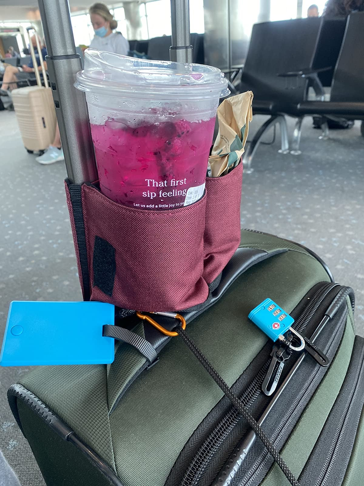 reviewer image of the cup holder attached to a suitcase with a Starbucks drink in it