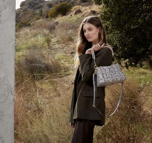 model holding the handbag over her shoulder