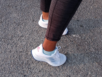 Reviewer showing back view of Adidas sneakers