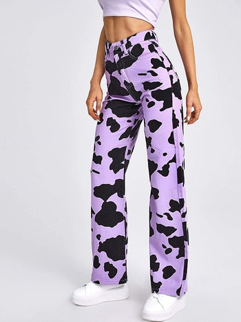 a model wearing the cow print pants in purple