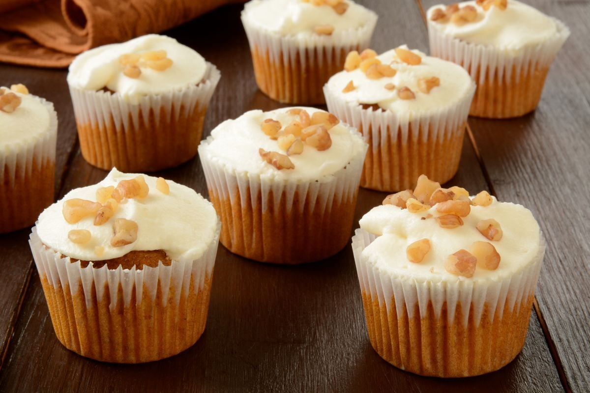 Carrot cake cupcakes topped with cream cheese frosting and walnuts