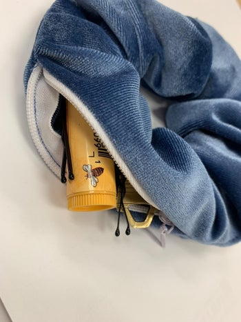 lip balm, pins, and other small items inside a reviewer's blue velvet scrunchie with zipper closure