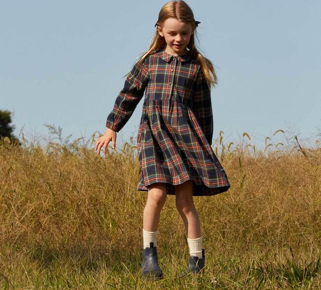 a child wearing a plaid dress with a collar and long sleeves