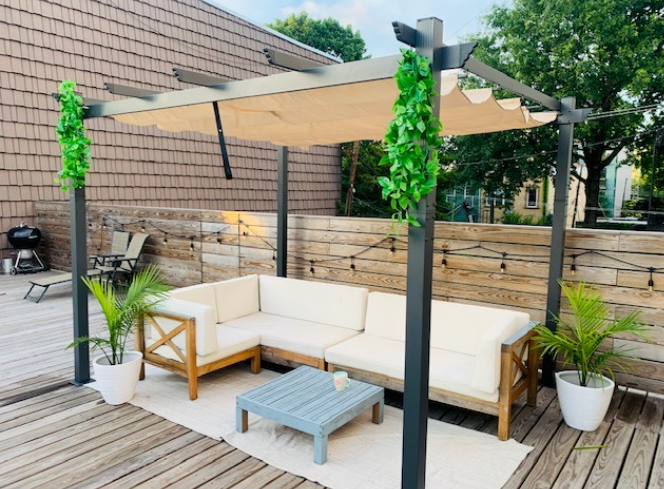 pergola set up in reviewer's backyard with a sectional styled under with planters and table