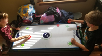kids playing with the air hockey table