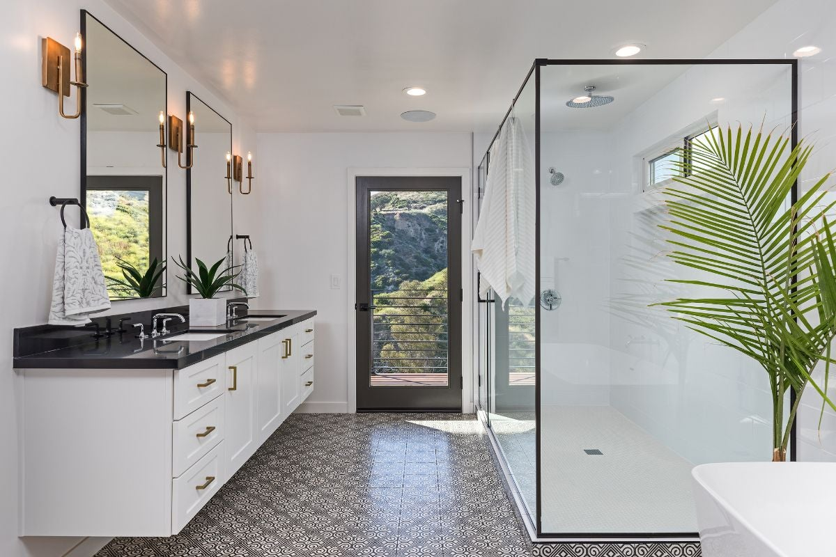 A bathroom with tile floors, a counter on the left, a large shower to the right, and a door at the end leading to a balcony