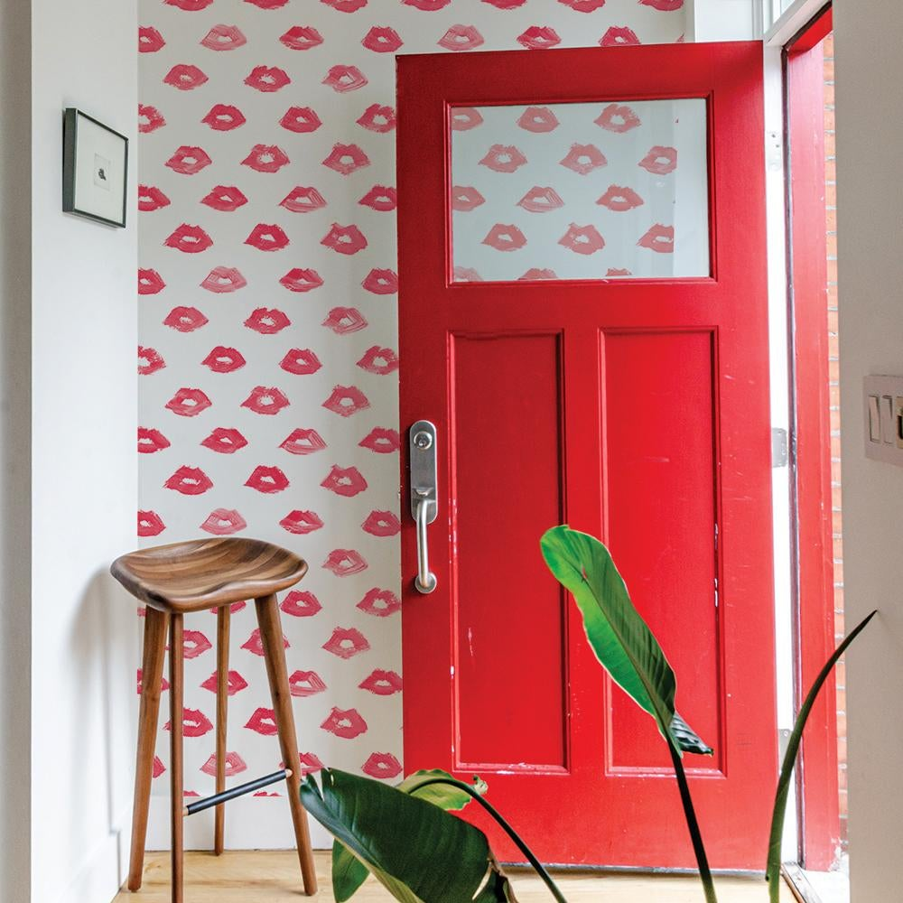white wallpaper with red lip print on an accent wall
